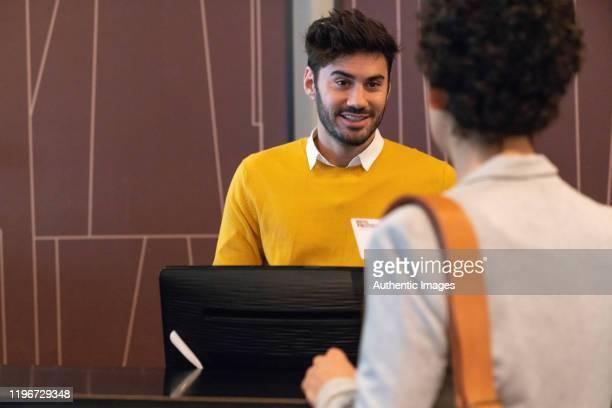 受付からホテルで鍵を受け取る女性ゲスト - ゲスト ストックフォトと画像
