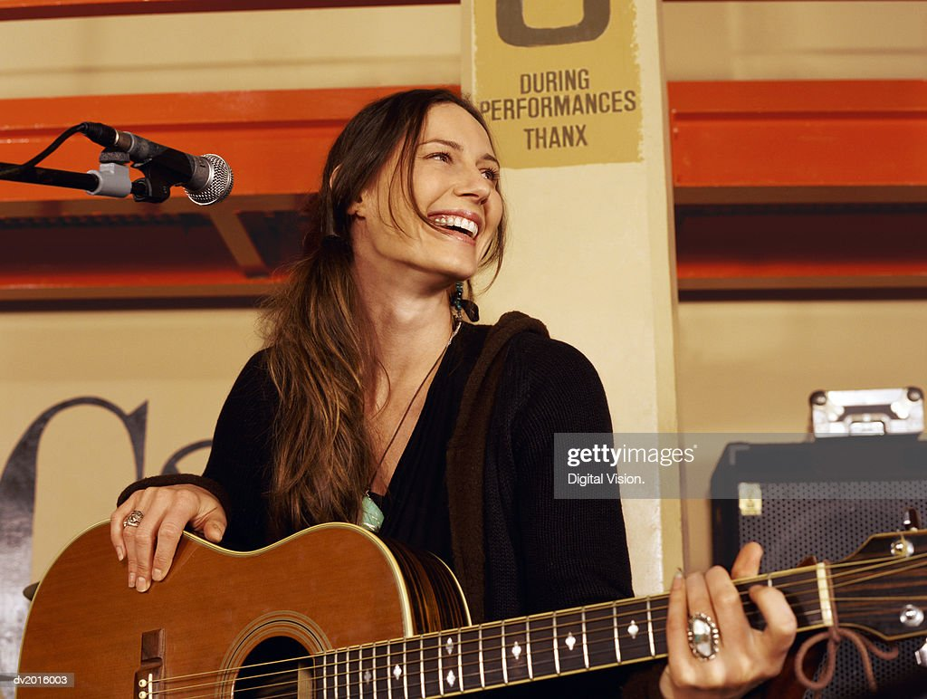 Female Guitarist Stands by a Microphone Stand on a Stage, Laughing : Stock Photo