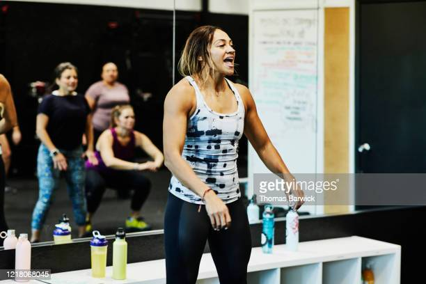 female gym owner leading womens fitness class - sportkleding stock pictures, royalty-free photos & images