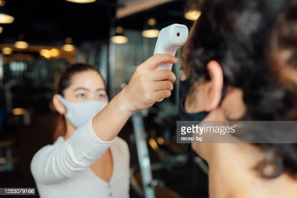 赤外線温度計を使用して顧客の体温を確認する女性ジムの所有者 - 検査業務 開始の地 ストックフォトと画像