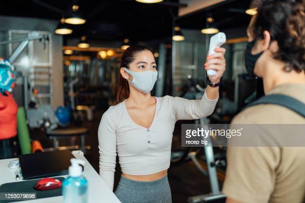 赤外線温度計を使用して顧客の体温を確認する女性ジムの所有者 - コントロール ストックフォトと画像