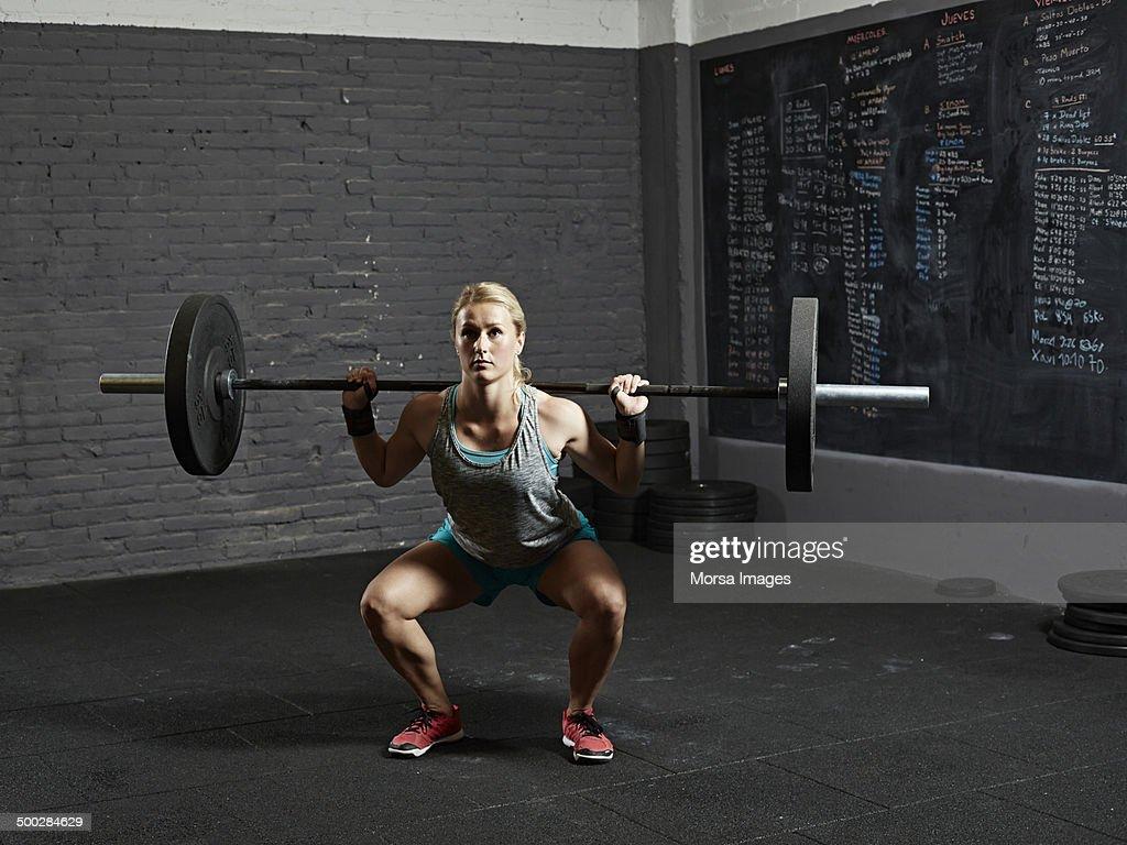 Female gym performing back squat : Stock Photo