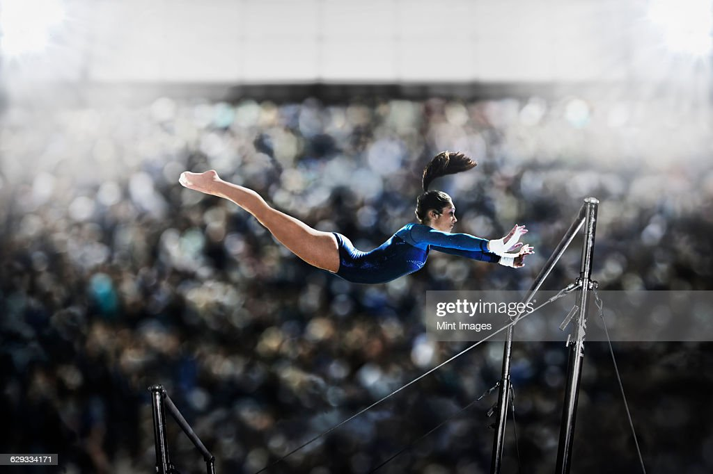 A female gymnast, a young woman performing on the parallel bars, in mid flight reaching towards the top bar.  : Stock Photo