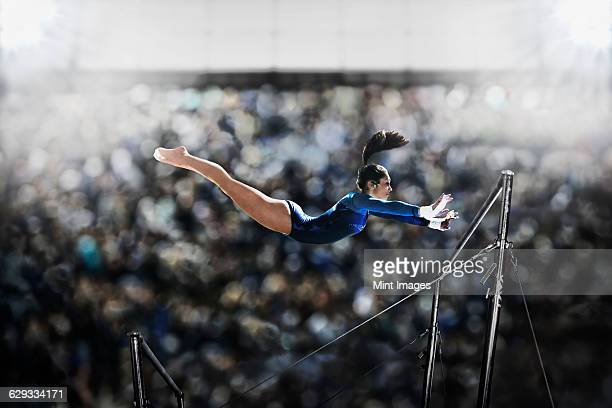 a female gymnast, a young woman performing on the parallel bars, in mid flight reaching towards the top bar.  - gymnastics stock pictures, royalty-free photos & images
