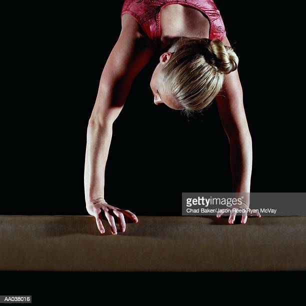 Female gymnast balanced on vault