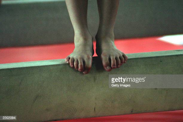 A female gymnast balances her feet on the balance beam during the daily afternoon training at the state owned Shichahai sports school July 25 2003 in...