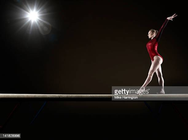 female gymnast balancing on beam - gymnastics stock pictures, royalty-free photos & images