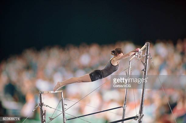 female gymnast competing on the uneven bars in front of a large crowd - horizontal bars stock pictures, royalty-free photos & images