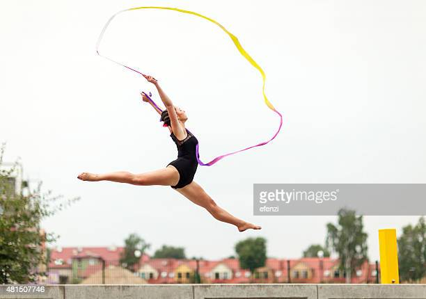 female gymnast dancing outdoors with ribbon - rhythmic gymnastics stock pictures, royalty-free photos & images