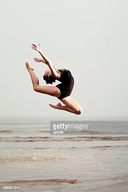 Female gymnast exercising at the seaside