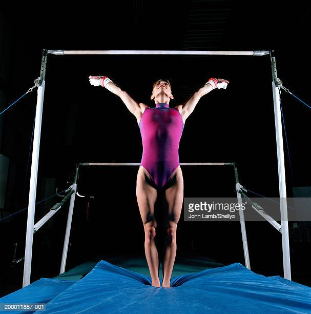 female gymnast in front of asymmetric bars, arms raised - gymnastics stock pictures, royalty-free photos & images