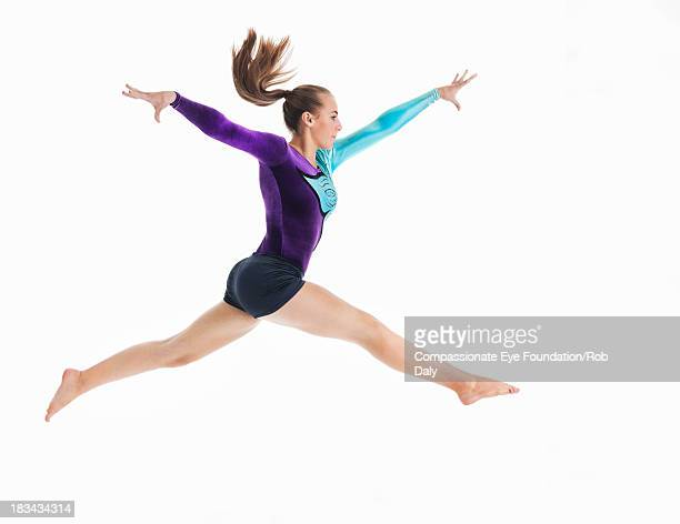 female gymnast jumping in mid-air - gymnastics stock pictures, royalty-free photos & images