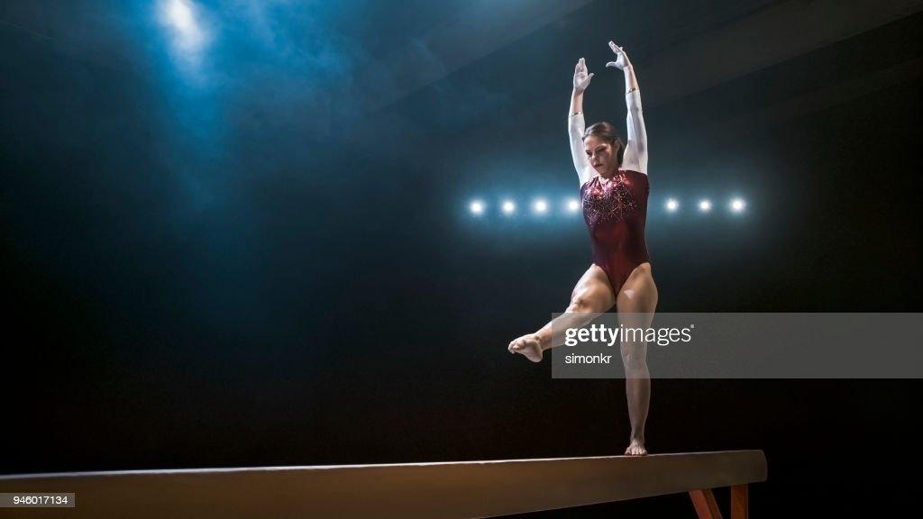 Femme gymnaste sur la poutre d'équilibre : Photo