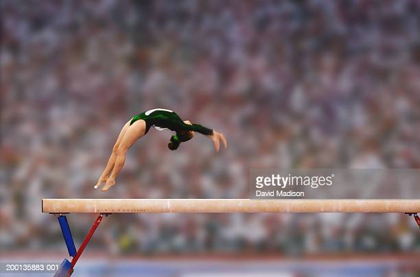 Female gymnast performing back flip on balance beam