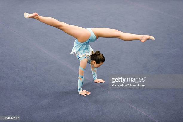 Female gymnast performing handstand