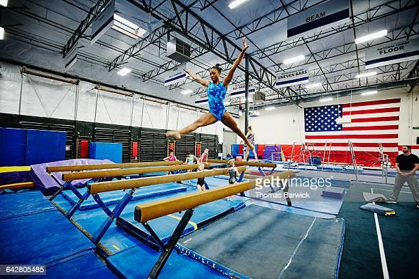 female gymnast performing on balance beam in gym - gymnastique au sol photos et images de collection