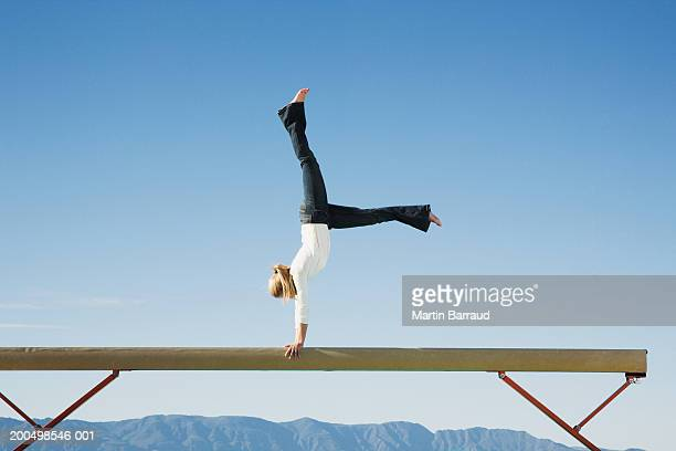 female gymnast performing on balance beam, side view - balance beam stock pictures, royalty-free photos & images
