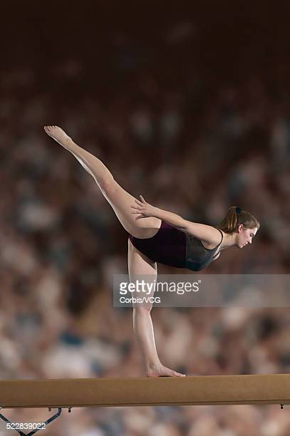 female gymnast performing on the balance beam in front of a large crowd - balance beam stock pictures, royalty-free photos & images