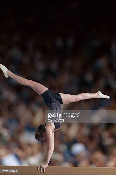 Female gymnast performing on the balance beam in front of a large crowd