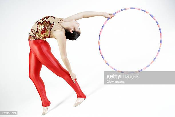 Female gymnast practicing with a plastic hoop