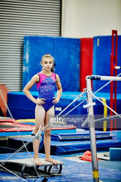 Female gymnast resting between bar exercises