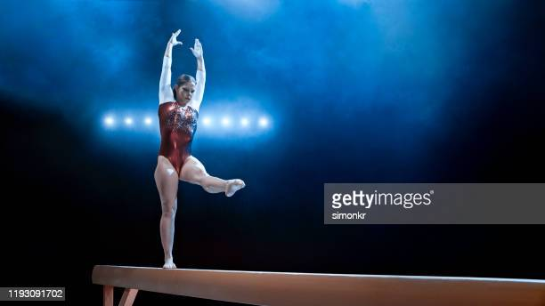 female gymnast standing on balance beam - balance beam stock pictures, royalty-free photos & images