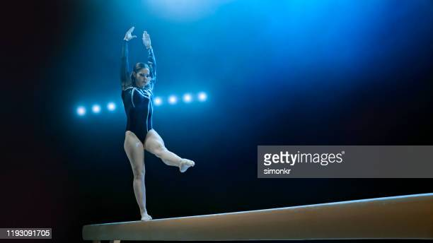 female gymnast standing on balance beam - gymnastics stock pictures, royalty-free photos & images