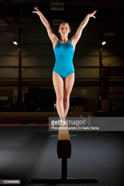 Female gymnast standing on balance beam