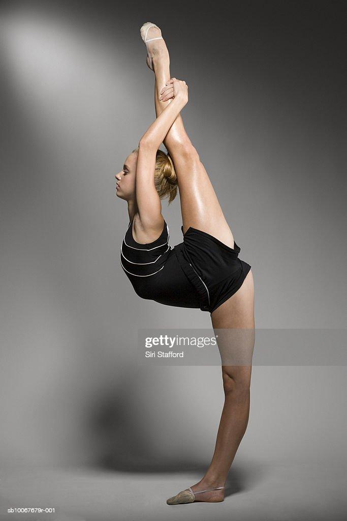 Female gymnast stretching, studio shot : Stock Photo