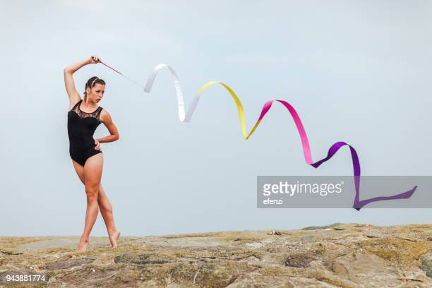 female gymnast training with ribbon outdoors at sea - artistic gymnastics stock pictures, royalty-free photos & images