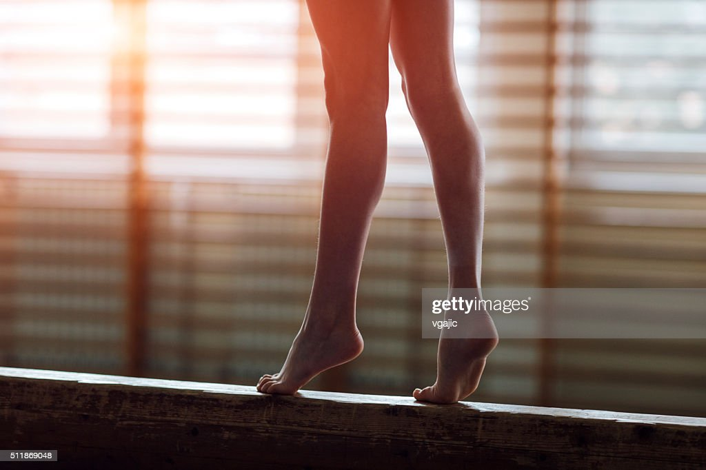 Female gymnast walking on balance beam, low section : Stock Photo