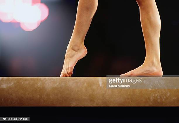 Female gymnast walking on balance beam, low section