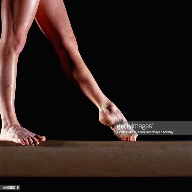 Female gymnast walking on balance beam, low section, side view
