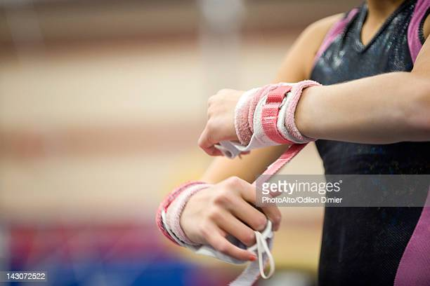 female gymnast wrapping wrists in preparation, cropped - gymnastics stock pictures, royalty-free photos & images