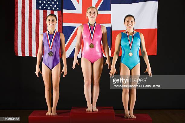 Female gymnastic medalists stanidng on winner podium, portrait