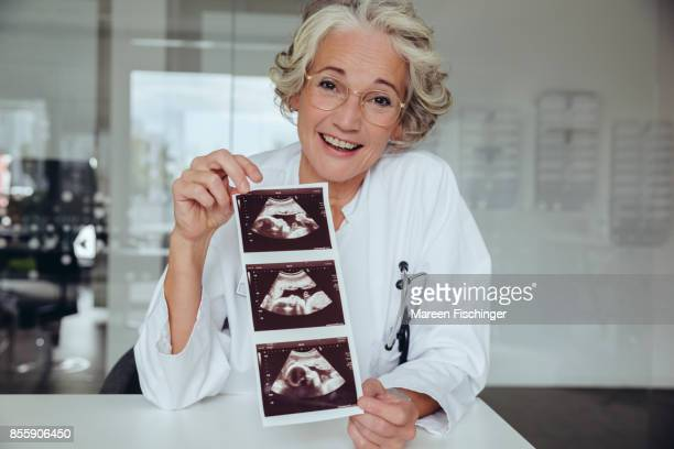 Female gynaecologist happily holding up ultrasound pictures of fetus