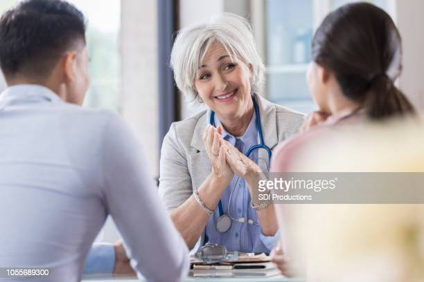 female gynecologist talks with young couple - human fertility stock pictures, royalty-free photos & images