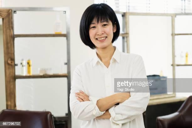 自分のヘアサロンで働く女性の毛スタイリスト オーナー