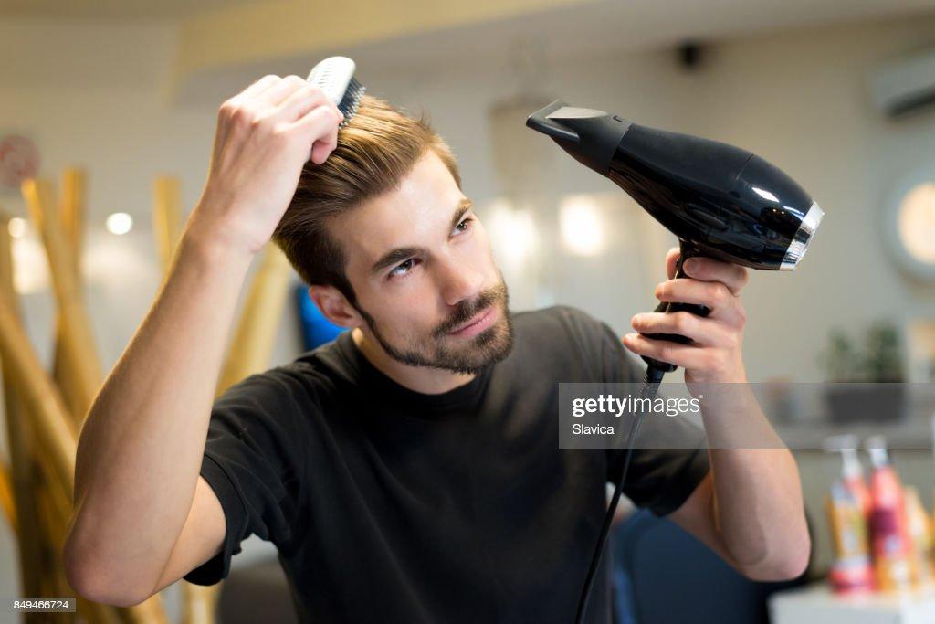 Cabeleireiro feminino, pentear e secar seu próprio cabelo em salão de cabeleireiro : Foto de stock