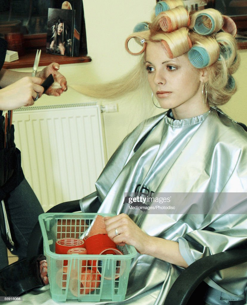 Female hairdresser cutting hair of a mid adult woman : Stock Photo