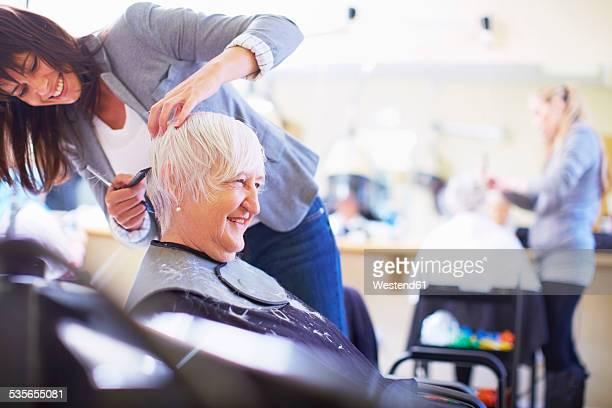 female hairdresser cutting hair of senior woman - kurzhaarschnitt stock-fotos und bilder