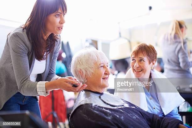 Female hairdresser cutting hair of senior woman