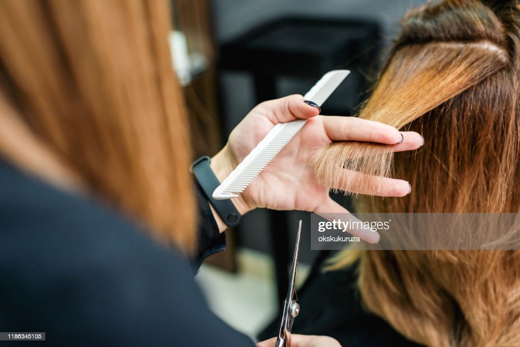 Vrouwelijke Kapper snijden vrouw haar close-up. : Stockfoto