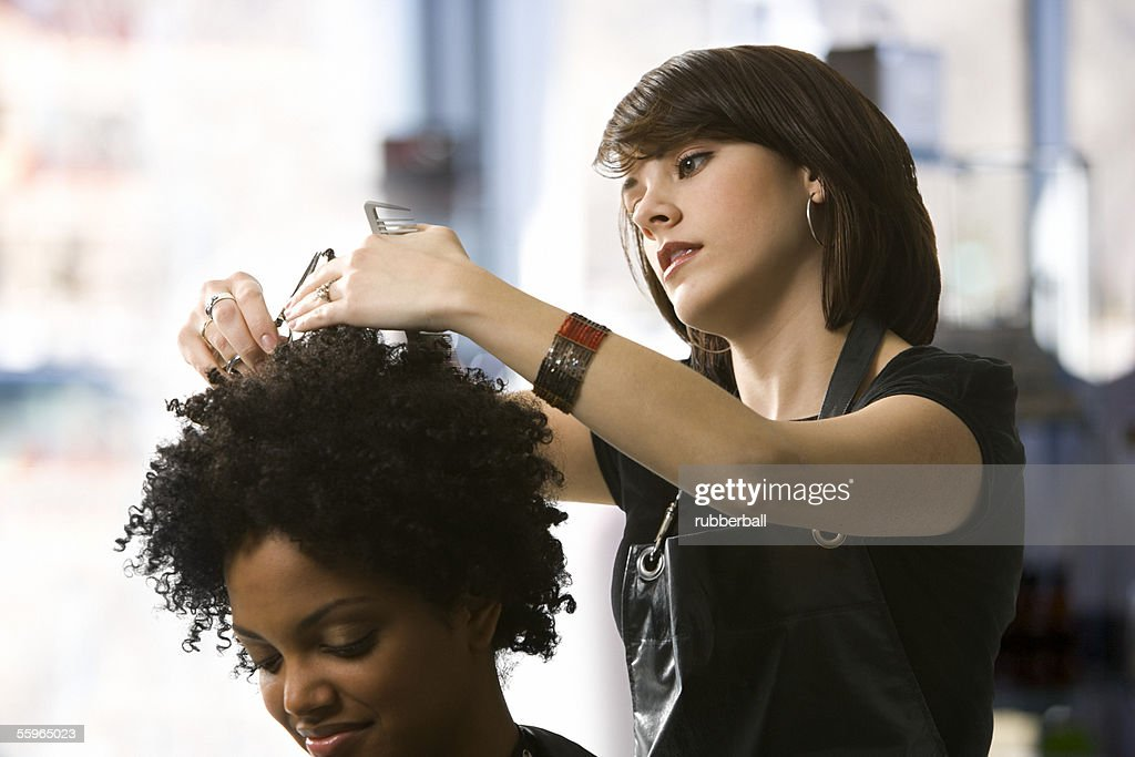 Female hairdresser trimming a young woman's hair : Stock Photo