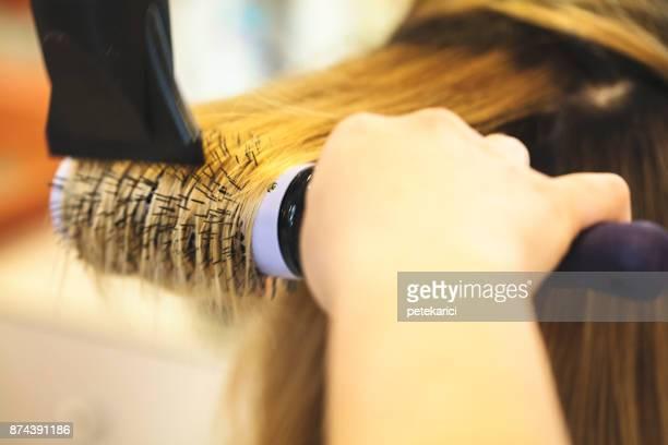Female hairdresser using hairbrush and hair dryer