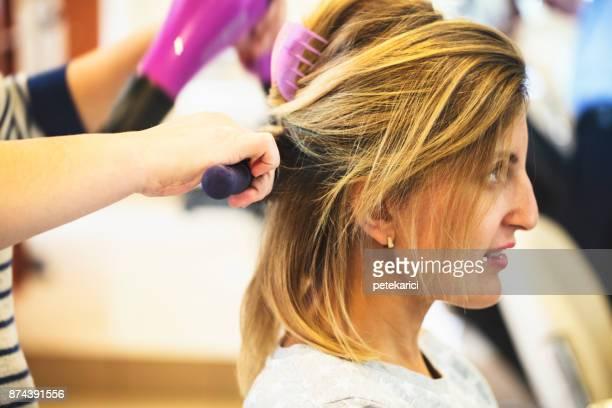 Weibliche Friseur mit Haarbürste und Haartrockner