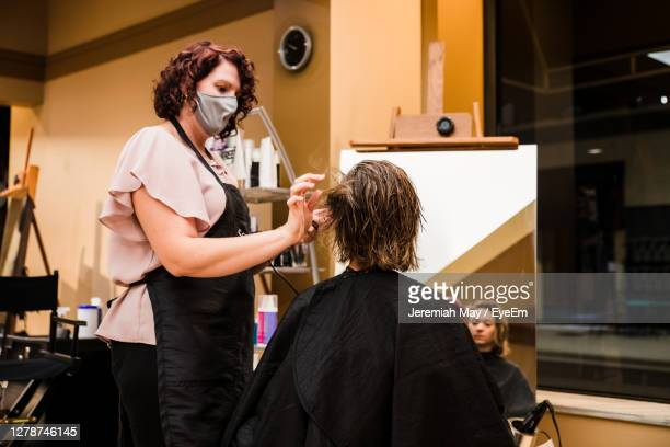 female hairdresser with face mask hairdressing of young woman in salon - ポートヒューロン ストックフォトと画像