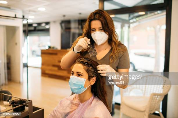 female hairdresser with mask staining hair of female customer with mask - hairdresser stock pictures, royalty-free photos & images