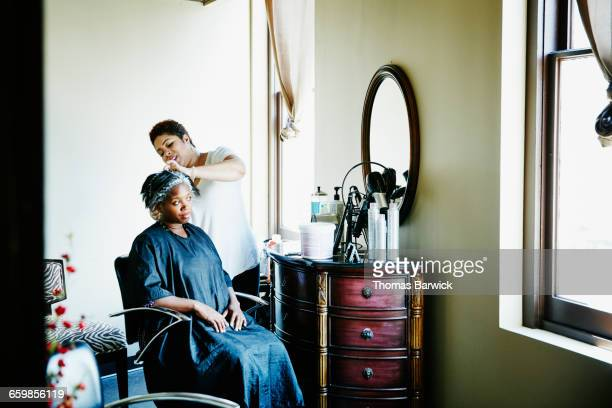 Female hairstylist foiling clients hair in salon
