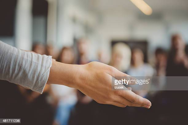 Female hand against defocused group of students